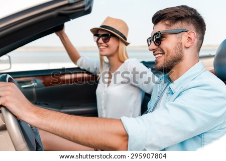 Our time for adventure. Side view of joyful young man driving convertible while his girlfriend sitting near on the front seat  - stock photo