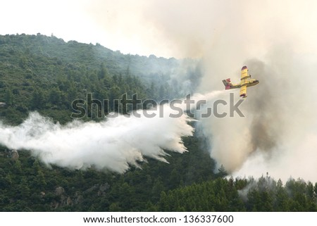 OURANOUPOLI, GREECE - AUGUST 9: A firefighting plane releases its load of water as it tries to extinguish a fire near the village of Ouranoupolis on August 9, 2012 in Ouranoupoli, Greece