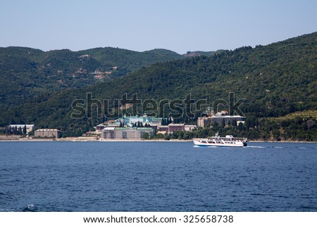 Ouranoupolis , Greece - June, 1, 2015: Russian St. Panteleimon's Orthodox monastery at Mount Athos, Agion Oros, Holy Mountain, Halkidiki , Greece and the ship near it - stock photo