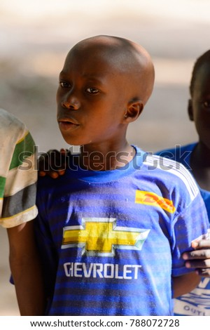 OUSSOUYE, SENEGAL - APR 30, 2017: Unidentified Senegalese little boy in striped shirt looks at something  in the Sacred Forest near Kaguit village