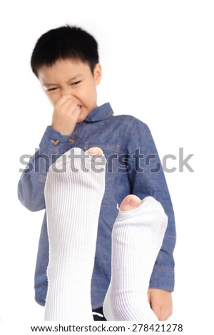 Out focus  Boy feeling unhappy with bad smell white sock