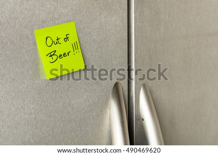 Out of beer reminder sticky note on a home refrigerator.