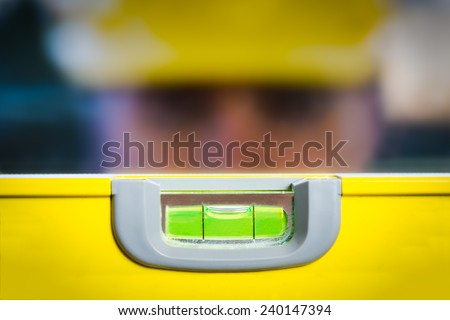 Out of focus construction worker behind a level which is in focus.  - stock photo