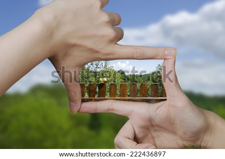 out of focus empty nature landscape and fingers creating a square making the vision of the future clear