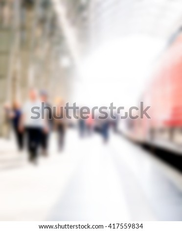 Out of focus group of people leaving a train at railway station and walking by the platform. The scene is blurred and brightly lit and the people are unrecognizable. - stock photo