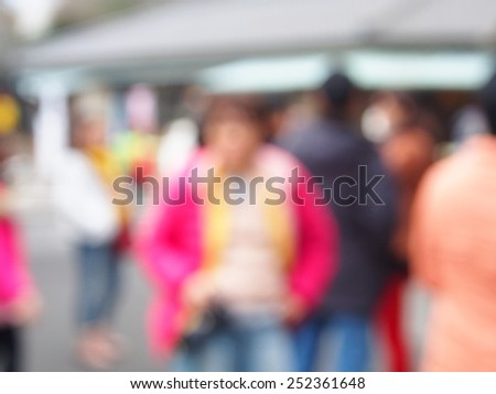 out of focus picture of a crowd of people walking in the city - stock photo