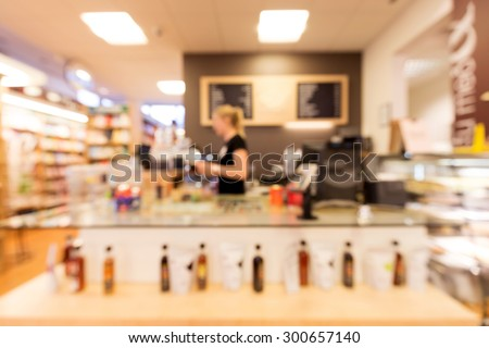 Out of focus shot of a person working at a sales counter in a bookstore / coffee shop - stock photo