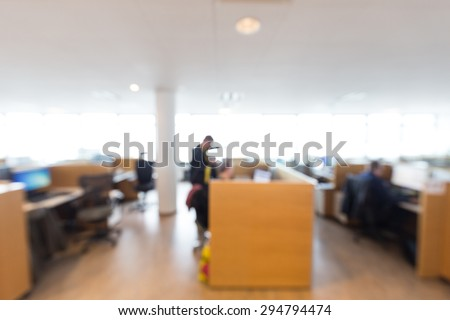 Out of focus shot of office workers working together on a project, overexposed windows in the background - stock photo