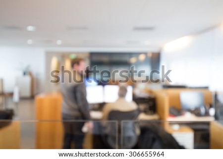 Out of focus shot of two coworkers working together in an office setting - stock photo