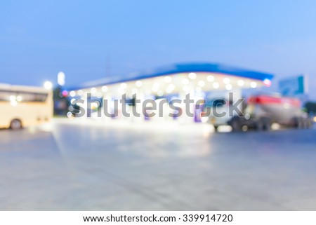 out of focus twilight gas station with bus and concrete truck - stock photo