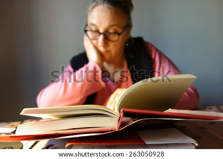 out of focus woman reading a book - stock photo