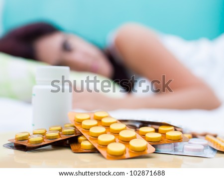 Out of focus woman resting in bed with some pills from her medical treatment on a table in the foreground - stock photo