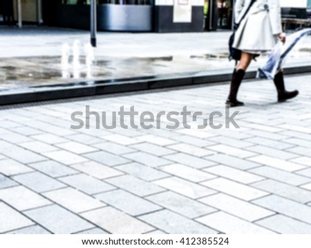out of focus young woman walking by on walkway - stock photo