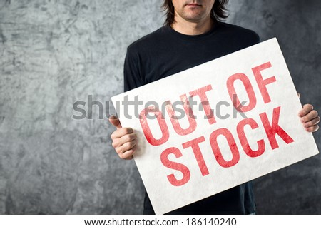 Out of Stock sign in hands of storage employee, shortage in supply chain