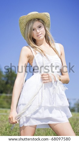 Outback Country Girl Wearing A Farming Hat Strikes A Pose While Holding Rope When Living On The Land - stock photo