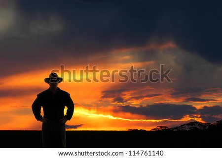 Outback cowboy at sunset - stock photo