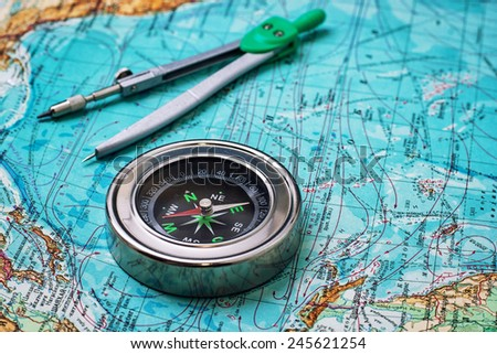 outdated compass sailor on a topographic map - stock photo