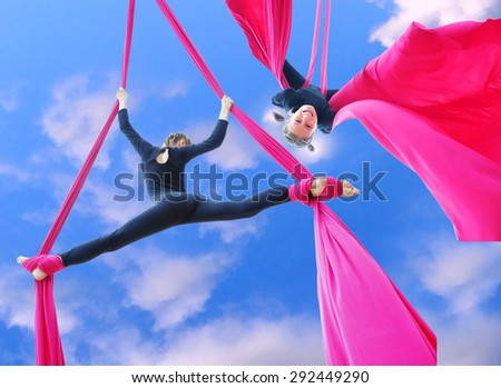 Outdoor activity of cheerful child training on aerial silks or ribbons in the sky.  Childhood, sports, active lifestyle concept. - stock photo