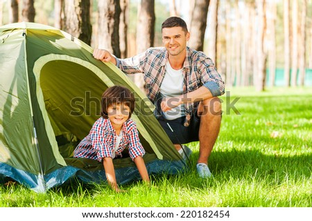 Outdoor adventure. Cheerful father and son sitting near the tent while camping in the forest   - stock photo