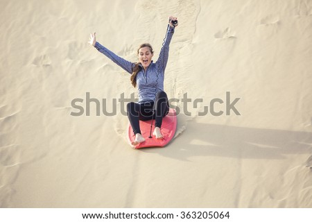 Outdoor Adventure seeker riding down a large sand dune with great speed and screaming with fun and excitement