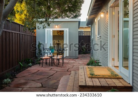 Outdoor area of traditional California home with french door leading to seating arrangement and shed / bungalow with matching design and colors.  - stock photo