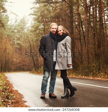 Outdoor autumn cold weather vintage photo of young beautiful couple in love posing in forest road together and having fun