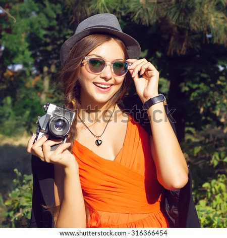Outdoor autumn fashion close portrait of young pretty stylish brunette woman posing at park,wearing trendy orange chiffon dress,black jacket,hat and sunglasses.Making photo and holding vintage camera. - stock photo