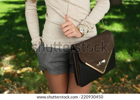 outdoor autumn fashion young trendy girl  with handbag clutch walking - stock photo