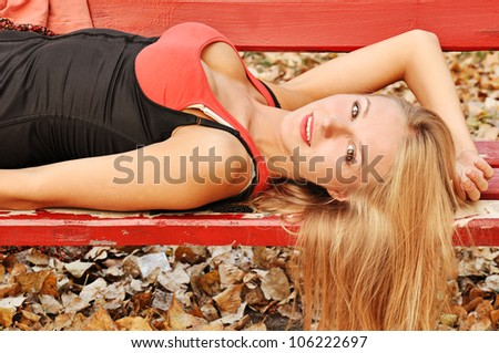 Outdoor autumn  portrait of beautiful sexy girl on the red bench