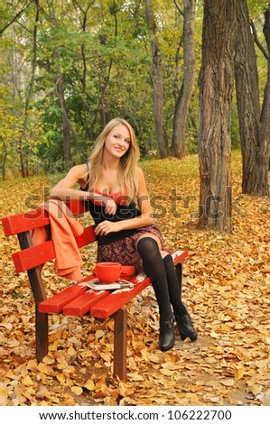 Outdoor autumn  portrait of beautiful sexy girl on the red bench - stock photo