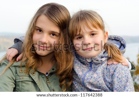 Outdoor autumn portrait of happy sisters - stock photo