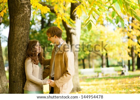 Outdoor autumn portrait of happy young couple - stock photo