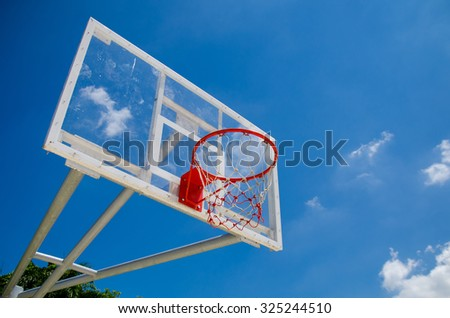 Outdoor basketball hoop on a holiday, casual and bright blue sky. - stock photo