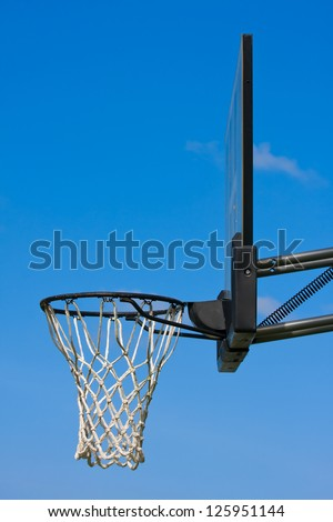 Outdoor basketball hoop set against a blue sky - stock photo