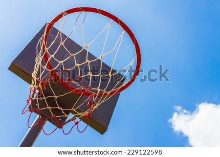 Outdoor basketball hoop with blue sky and clouds background