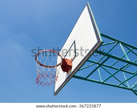 Outdoor basketball hoop with blue sky background
