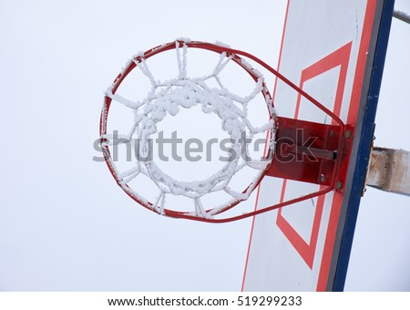 Outdoor basketball hoop with net, covered by hoarfrost