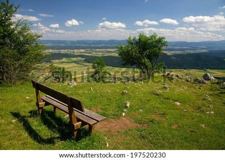 Outdoor bench in a nice mountain area - stock photo