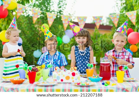 Outdoor birthday party for toddlers with colorful cake - stock photo