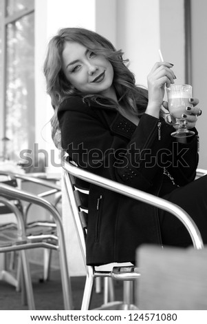 Outdoor black and white photography of smiley attractive young woman in street cafe on Beauty and Fashion theme - stock photo