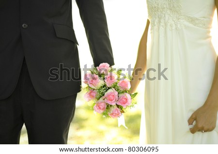 Outdoor Bride and Groom holding flower bouquet - stock photo