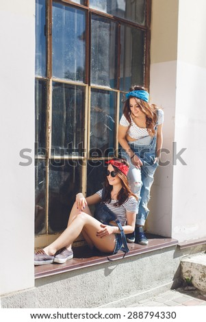 Outdoor bright summer portrait of stylish cheeky young hipster woman, sitting at windowsill, have long brunette hairs perfect tanned fit slim body, wearing denim overall bright bandana and sunglasses.