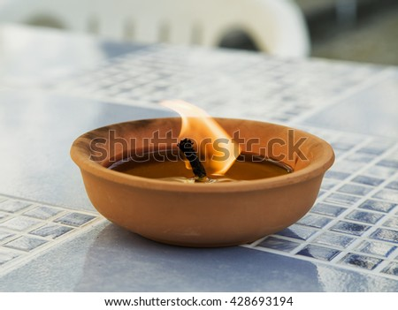 Outdoor burning candle over table, horizontal image
