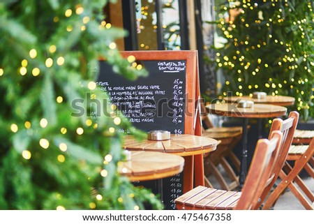 Outdoor cafe on a street of Paris decorated and illuminated for Christmas. Menu board with list of delicious French food. Seasonal winter holidays concept