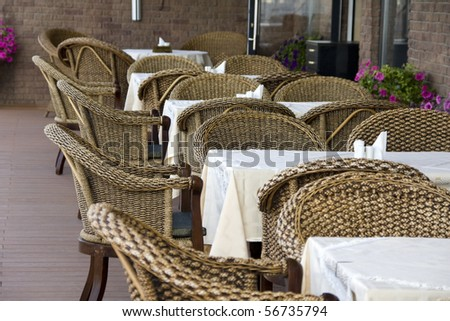 Outdoor cafe. Row of rattan chairs and tables - stock photo