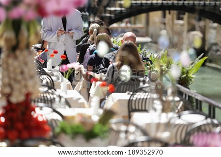 Outdoor cafe scene with waiter in white jacket taking order - stock photo