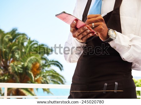Outdoor cafe scene with waitress taking order. Close up - stock photo