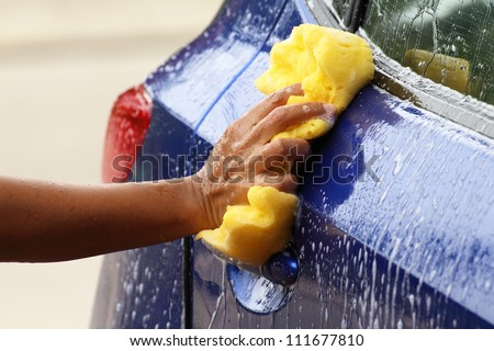 outdoor car wash with yellow sponge - stock photo