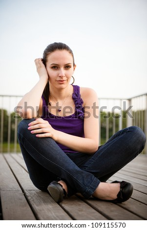 Outdoor casual portrait of young woman sitting on ground - stock photo
