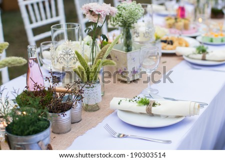 Outdoor catering dinner at the wedding with homemade garnishes decoration - stock photo